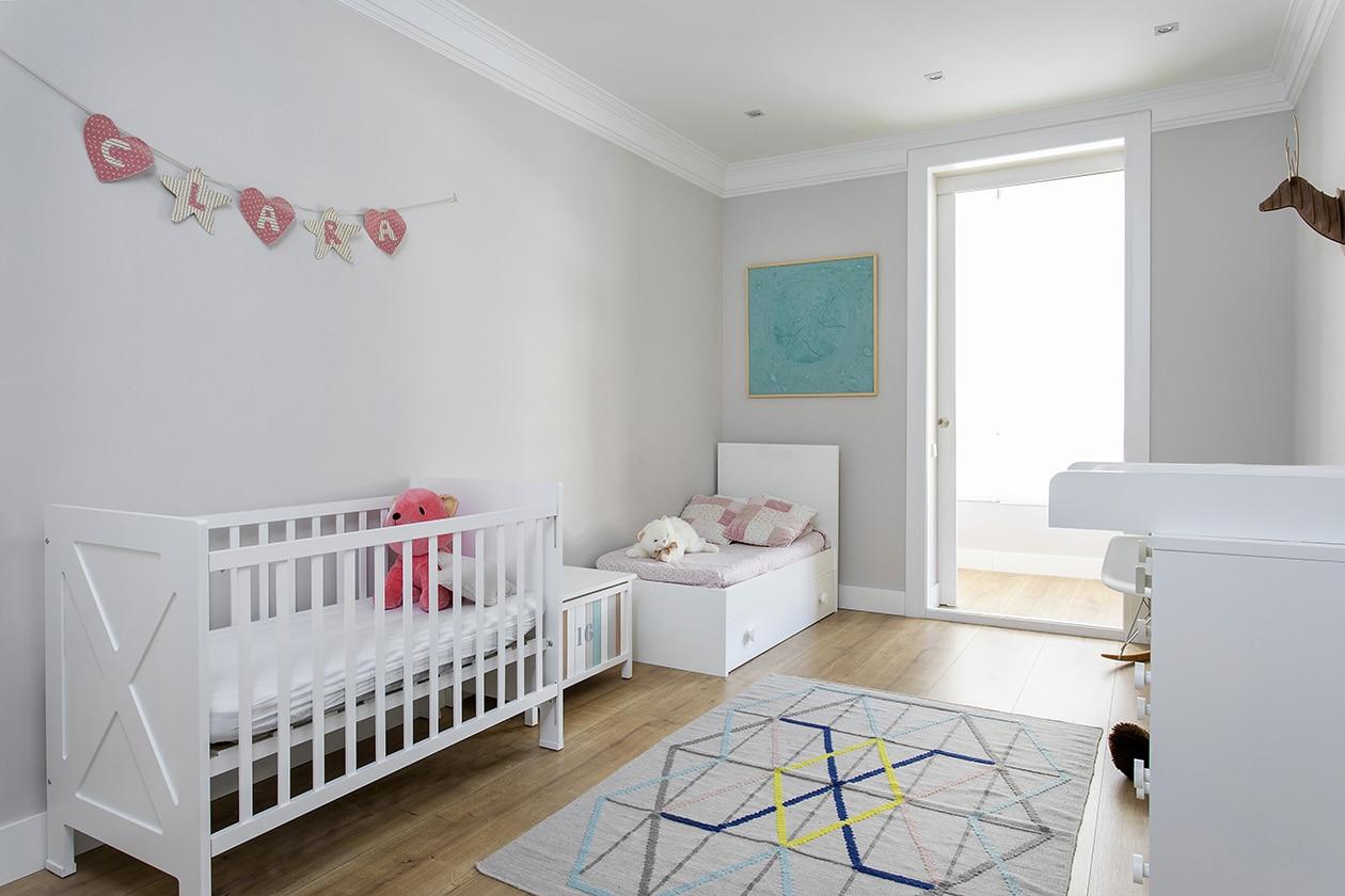 Habitación infantil con una cuna, los muebles para un bebé y decoración infantil muy clara