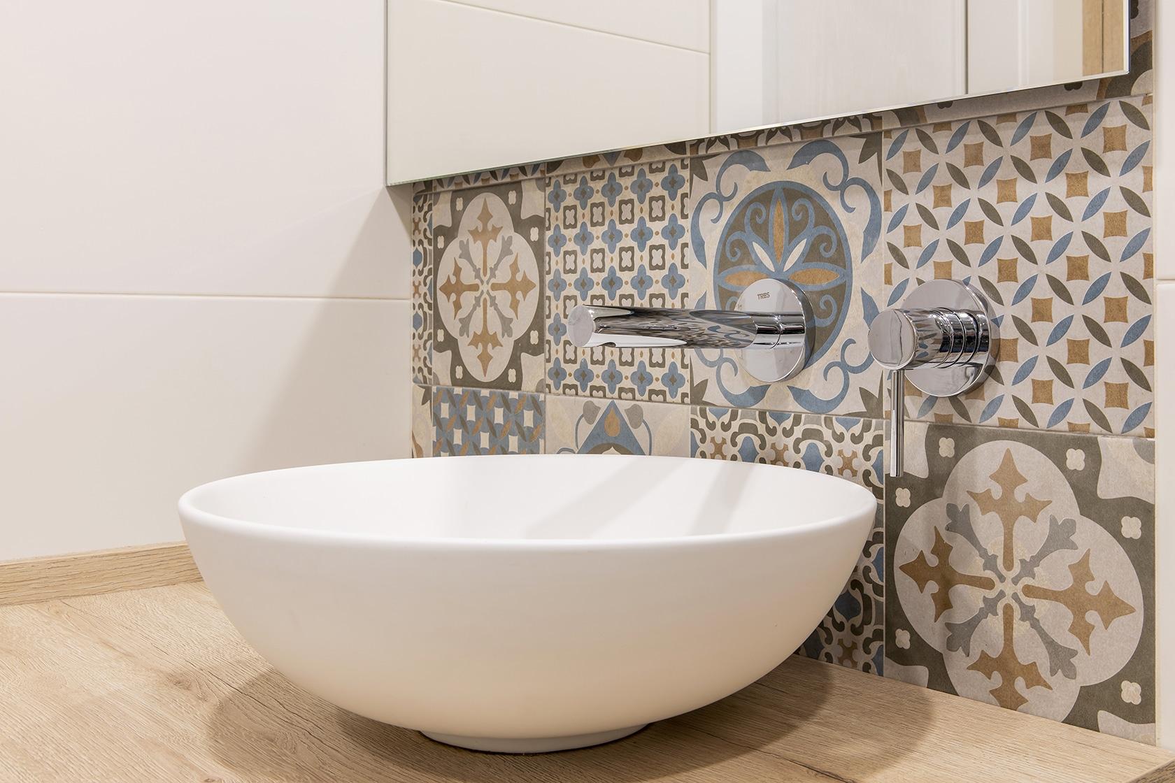 Pica del baño y encimera delante la pared de mosaico.