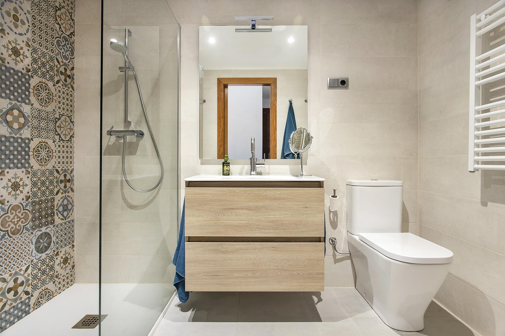 Vista general del baño. Inodoro a la derecha, pica con espejo y cajones en medio y ducha a la izquierda